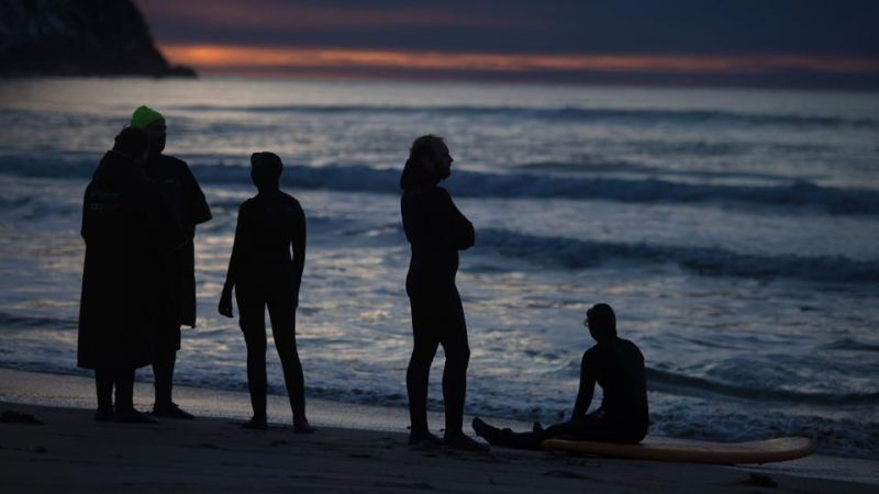 Surfers rest and enjoy the beautiful unset after surfing along the northern Atlantic Ocean.