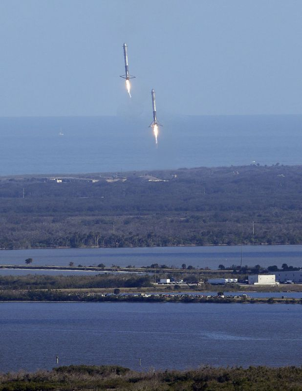 Two booster rockets from the Falcon 9 SpaceX heavy, return for a landing at the Kennedy Space Center in Cape Canaveral, Fla.