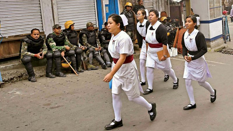 Nurses walk past armed security forces during the indefinite strike declared in Darjeeling (Photo: AP)