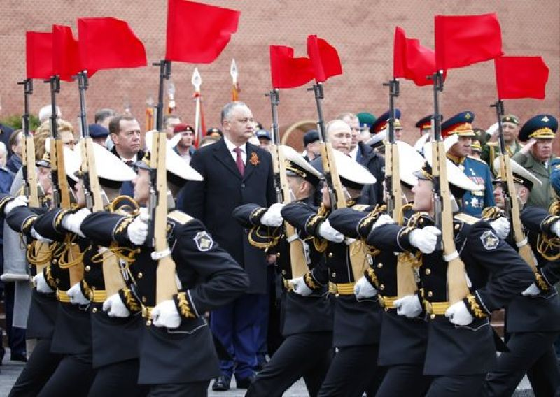 The Red Square parade is a highly ritualized display, and marked changes in its order are unusual. Moldovan President Igor Dodon, center, attends a wreath-laying ceremony at the Tomb of the Unknown Soldier in Moscow.
