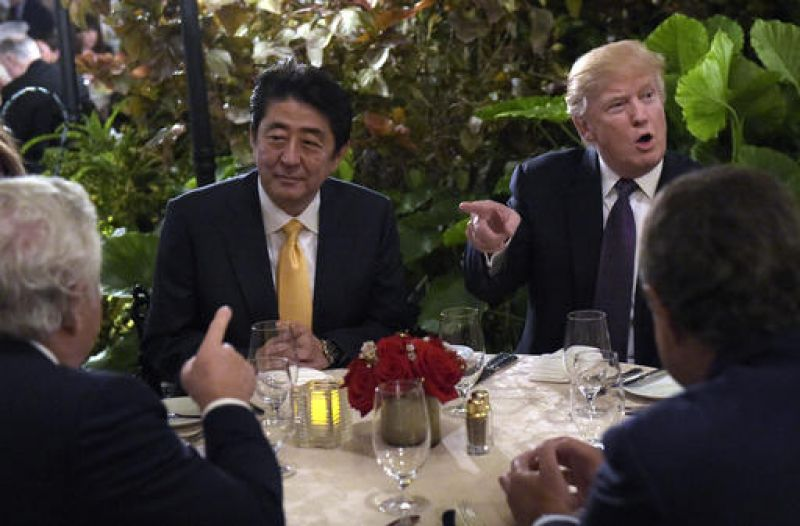 Donald Trump, Melania Trump, Robert Kraft, and Shinzo Abe sits down to dinner at Mar-a-Lago in Florida. Trump has dramatically shifted his stance on Asia in