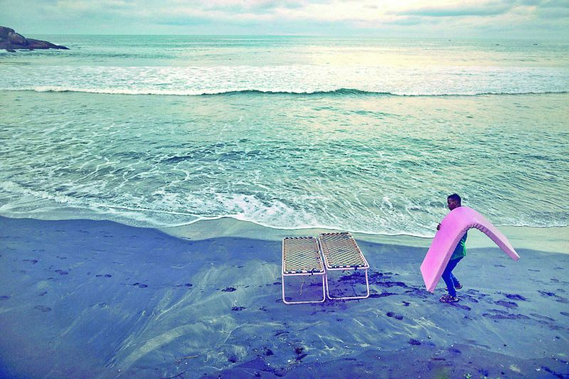 A man is setting up the table in the morning to welcome visitors at Light House beach, Kovalam, Kerala.