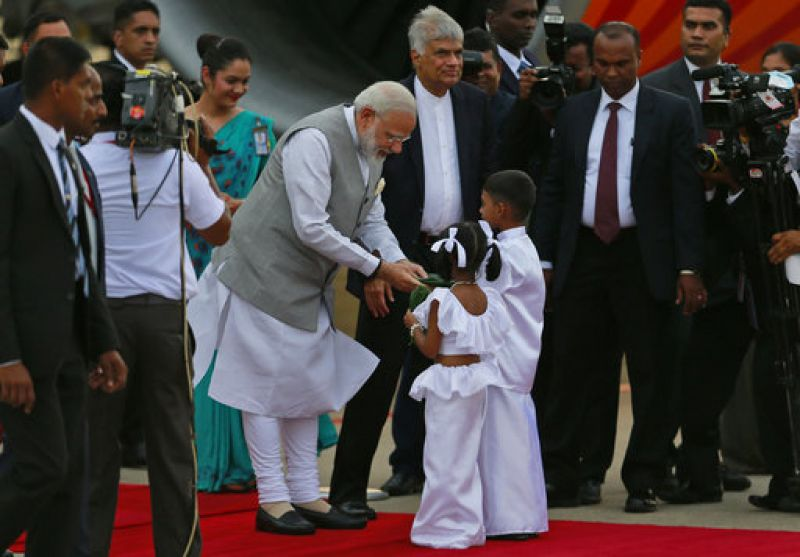 Prime Minister Narendra Modi receives betel leaves from two Sri Lankan children upon his arrival as Sri Lankan Prime Minister Ranil Wickremesinghe, center watches in Colombo.