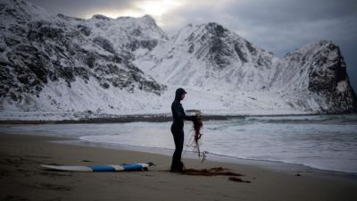 A novice surfer cleans his leash as he prepares for surfing.