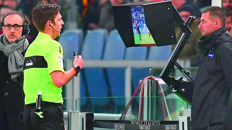 The on-field referee checks a replay on the monitor near the touchline.