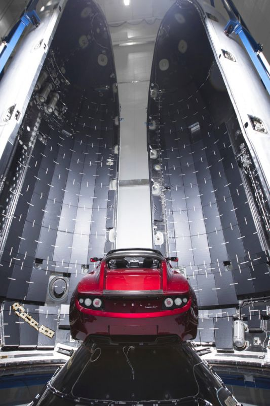 This photo shows a Tesla car next to the fairing of a Falcon Heavy rocket in Cape Canaveral, Fla. For the Heavy's inaugural flight, the rocket will carry up Elon Musk's roadster. In addition to SpaceX, Musk runs the electric car maker Tesla.