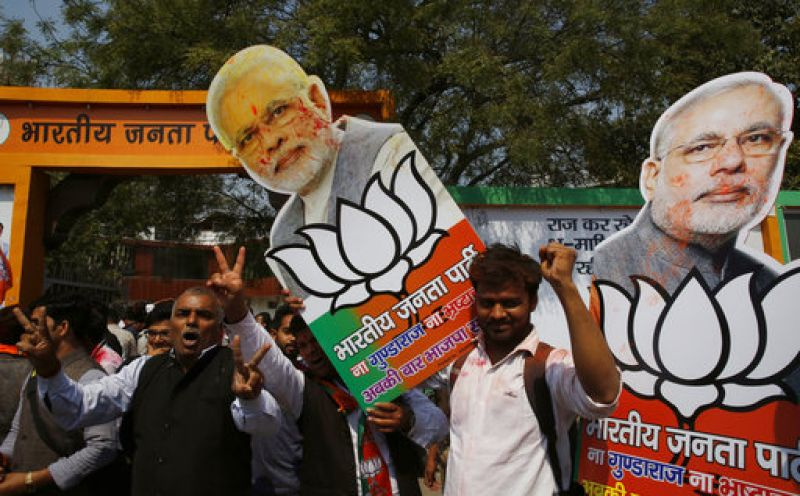 BJP supporters raise cutouts of Narendra Modi as they celebrate winning seats in the state of Uttar Pradesh in Lucknow.