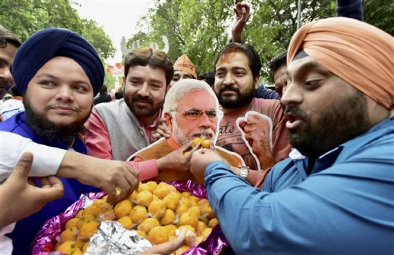 BJP supporters and workers offer sweets to a cut out of Prime Minister Narendra Modi as they celebrate party's victory in the assembly elections, at the party head quarters in New Delhi.