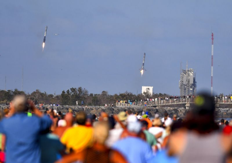 Crowds on the beach in Cape Canaveral watch two of the three boosters from the SpaceX Falcon Heavy launched from Kennedy Space Centre's Pad 39A land moments apart at Landing Zones 1 and 2 at Cape Canaveral Air Force Station.