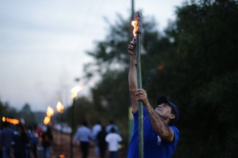 "A faithful Catholic lights a torch as he participates in the ""Tanarandy"" town procession, south of Asuncion, Paraguay. (Photo: AP)"