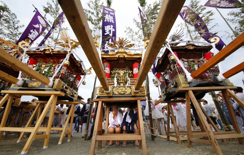 Participants sit under a portable shrine during a purification rite at the annual Hamaori Festival at Southern beach in Chigasaki, west of Tokyo Monday, July 17, 2017. (AP Photo/Shizuo Kambayashi)