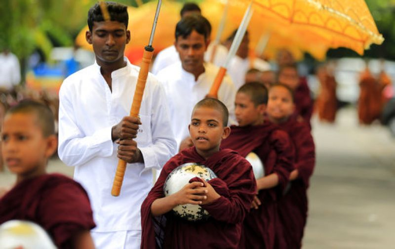 Buddhist monks walk in a procession for alms as part of a ritual during Buddha Purnima in Colombo,