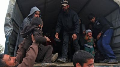 Displaced residents of western Mosul evacuate their neighbourhood , as Iraqi forces continue to advance in the embattled city combatting Islamic State (IS) group jihadists.