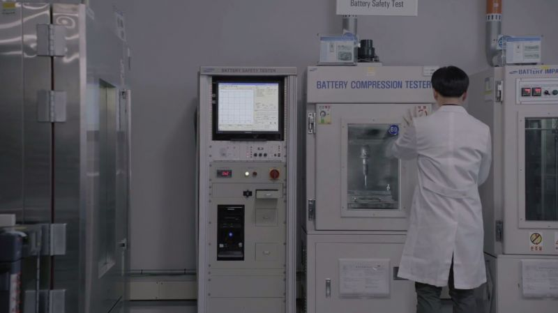 Samsung employee putting battery into Battery Compression Tester.