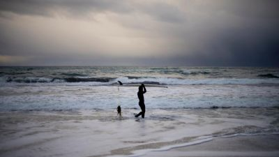 A surfer walks along the shore in Unstad.