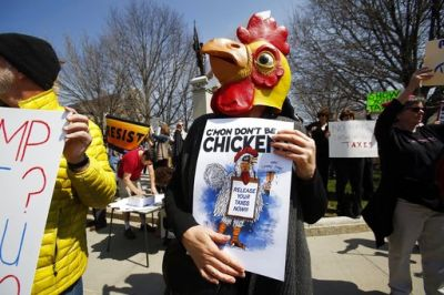 Many protesters suggested that the Republican president was afraid, or chicken, to publish his records. They hinted that it might have something to do with Russia.