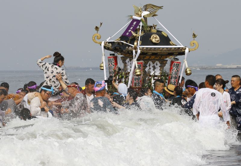 Carries crash through waves with the shrines on their shoulders as they parade through the sea during a purification rite at the annual Hamaori Festival at Southern beach in Chigasaki, west of Tokyo Monday, July 17, 2017. (AP Photo/Shizuo Kambayashi)