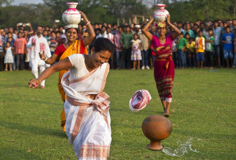 An Indian tribal woman reacts after an earthen pot filled with water falls off her head during a hundred meters run event with water pots on head, during the Suwori Tribal festival in Boko, Assam. (Photo: AP)