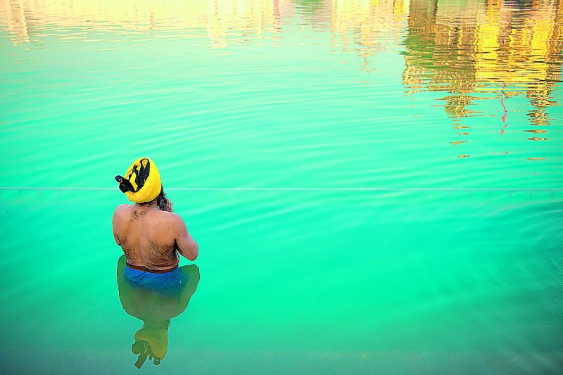 A devotee taking an early morning dip in cold waters at Golden Temple, Amritsar.