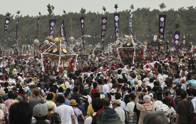The shrines are carried by people through crowds who have come to see the festivities to see the purification rite at the annual Hamaori Festival at Southern beach in Chigasaki, west of Tokyo Monday, July 17, 2017. (AP Photo/Shizuo Kambayashi)