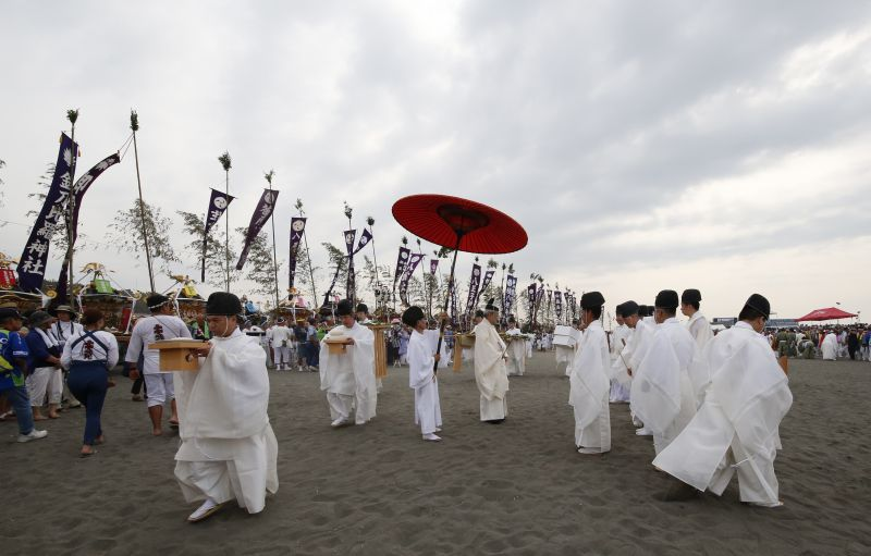 Shinto priests walk with tributes during a purification rite at the annual Hamaori Festival at Southern beach in Chigasaki, west of Tokyo Monday, July 17, 2017. (AP Photo/Shizuo Kambayashi)
