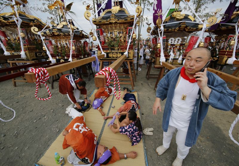 A participant uses a smartphone in front of the portable shrine during a purification rite at the annual Hamaori Festival at Southern beach in Chigasaki, west of Tokyo Monday, July 17, 2017. (AP Photo/Shizuo Kambayashi)