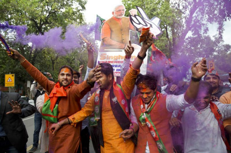 BJP supporters celebrate as their party leads in state elections in Uttarakhand and Uttar Pradesh states in New Delhi.