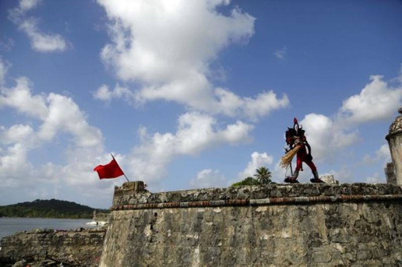 "A man, wearing a ""devil"" costume dance on a wall of the San Jeronimo fort during the Congos and Devils festival in Portobelo (Photo: AP)"
