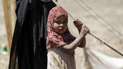 A Yemeni girl awaits humanitarian aid supplies given by the Russian humanitarian relief mission in a camp on the outskirts of the capital Sanaa.