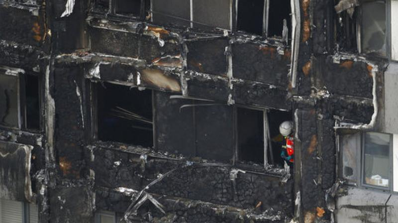 A firefighter stands outside of the Grenfell Tower after fire engulfed the 24-storey building, in London. (Photo: AP)