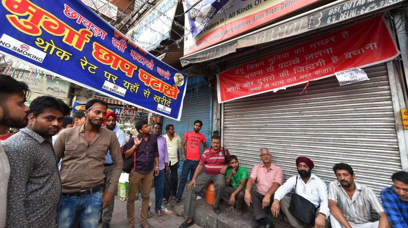 Shopkeepers sitting outside their closed shops of firecrackers at Sadar Bazar in New Delhi on Monday. (Photo: PTI)