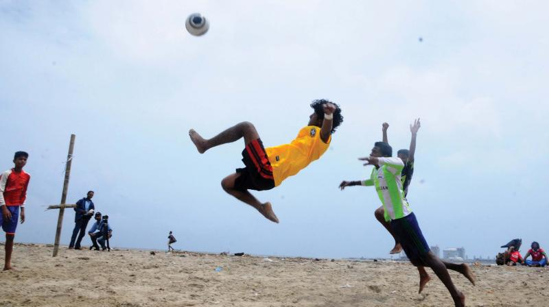 Young guys play football on the beach. (Photo: DC)