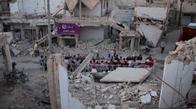 The tables laden with food to break the Ramadan fast are surrounded by the crumbling carcasses of bombed-out buildings.
