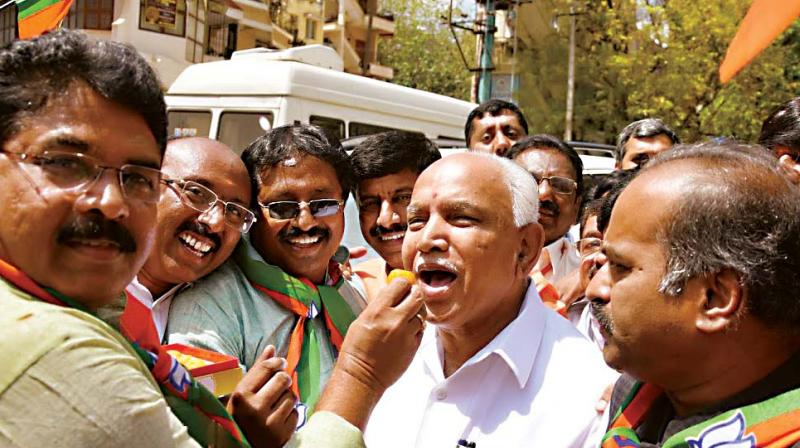 Senior BJP leaders R. Ashok, B.S. Yeddyurappa and P.C. Mohan celebrate party's victory in UP and Uttarakhand assembly elections, in Bengaluru on Saturday – DC