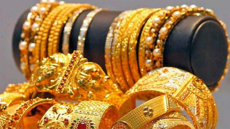 In worldwide trade, gold futures settled lower as the dollar climbed on the back of upbeat US retail sales data, but scored their first weekly gain in three weeks.