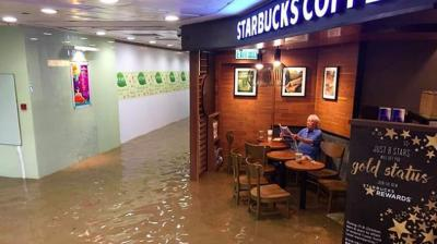 Honk Kong faced massive floods this week due to heavy rainfall but that didn't deter thisold man from enjoying his newspaper and coffee (Photo: Imgur)