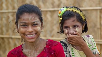 A Rohingya girl Ismat Ara, right, and her friend Roshimin Begum mile as they react to the camera at Thaingkhali refugee camp (Photo: AP)