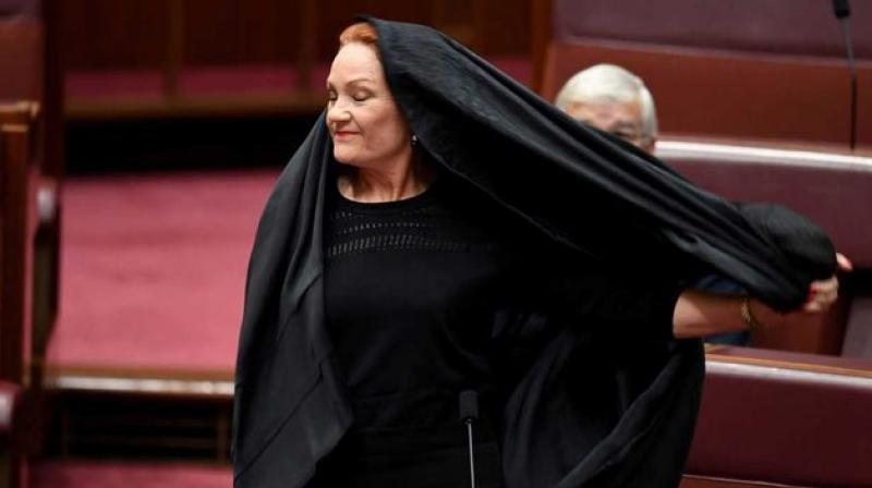 Pauline Hanson, leader of the anti-Muslim, anti-immigration One Nation minor party, sat wearing the black head-to-ankle garment for more than 10 minutes before taking it off as she rose to explain that she wanted such outfits banned on national security grounds. (Photo: Twitter)