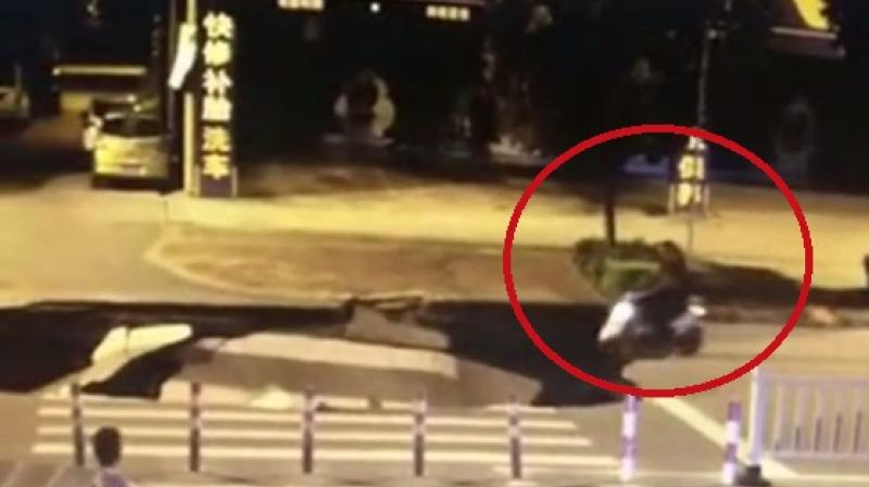 Unobservant motorcyclist drives straight into sinkhole in China