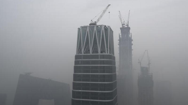 China's state broadcaster China Central Television (CCTV) headquarters and construction buildings at the Central Business District are shrouded by heavy smog in Beijing. (Photo: AP)