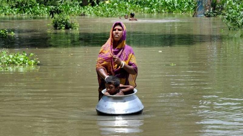 A woman with her child, in a utensil, moves to a safer place from the flood affected Khanamukh village in Morigoan, Assam on Wednesday.