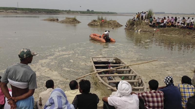 Rescuers search in the Yamuna River as villagers gather after a country boat, seen in foreground, capsized near Baghpat town in Uttar Pradesh on Thursday. (Photo: AP)