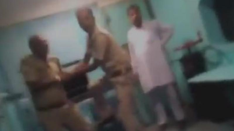Uttar Pradesh policeman is being thrashed by a Railway Police Force (RPF) jawan while jumping off a train to catch a fleeing prisoner. (Photo: ANI | Screengrab)