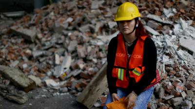 Frida Islas Rueda, 22-year-old student, poses for a picture near debris from a damaged building after an earthquake in Mexico City. At just 22, Islas has no recollection of the devastating 1985 earthquake that left thousands dead in Mexico City.