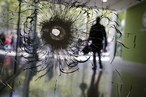 An attacker with an automatic weapon opened fire on police on Paris' iconic Champs-Elysees on Thursday night, killing one officer and seriously wounding three others before police shot and killed him. A bullet hole is pictured on a shop window of the Champs Elysees. (Photo: AP)