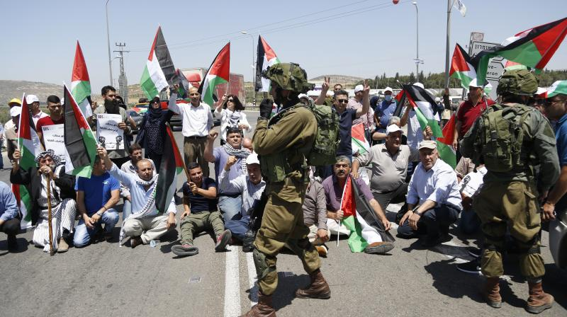 Palestinians protestors hold national flags during protest in solidarity with Palestinian prisoners on hunger strike in Israeli jails. (Photo: AP)