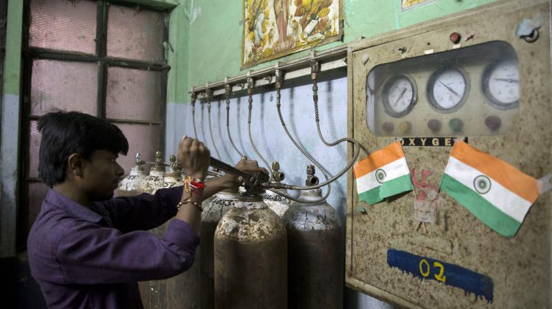 A hospital staff member checks newly arrived oxygen cylinders at Baba Raghav Das Medical College Hospital in Gorakhpur, in the northern Indian state of Uttar Pradesh. (Photo: AP)