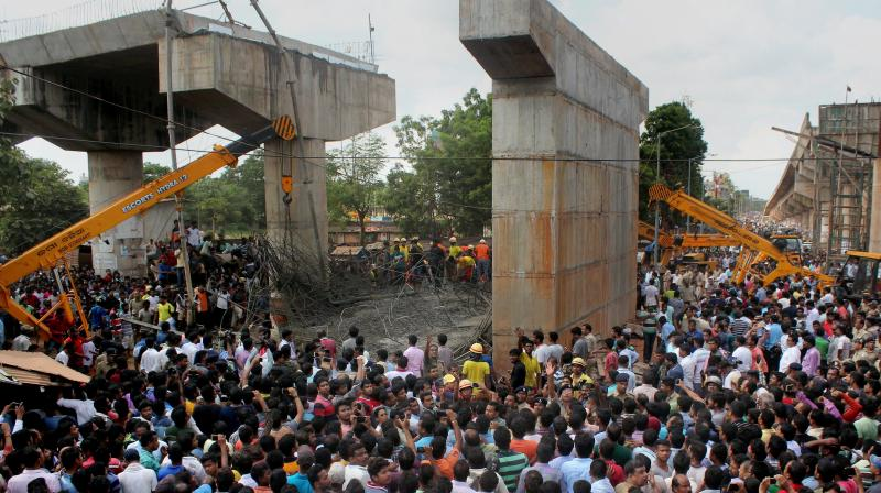 People crowd near the site of mishap where an under-construction ovebridge collapsed at Bomikhal in Bhubaneswar