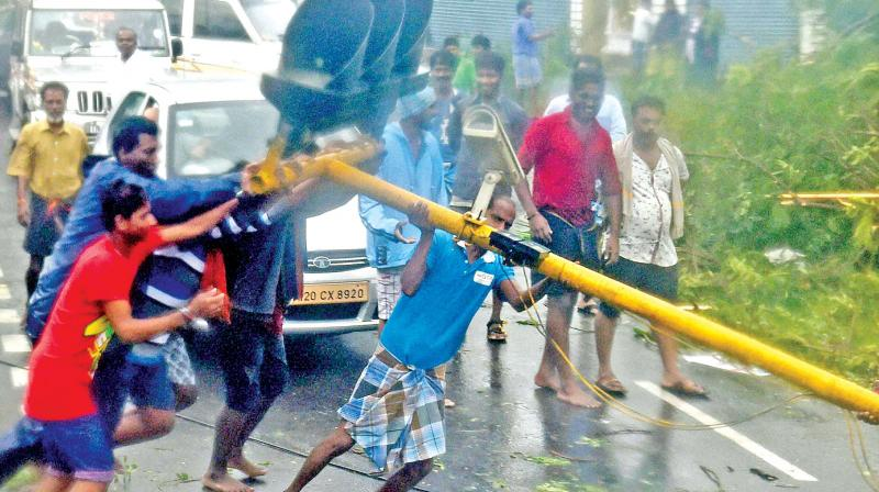 People lifting uprooted poles following a storm in Chennai on Monday. The movement of traffic on  several arterial roads including the famous Anna Salai, Grand Southern Trunk road were  largely affected while several trees were also uprooted as cyclone Vardah made landfall near Chennai coast on Monday.
