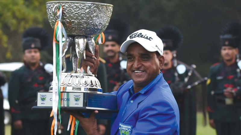 Mukesh Kumar poses with the trophy after winning the Panasonic Open India in New Delhi on Sunday. (Photo: AFP)